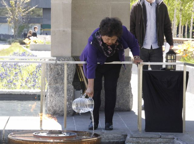 Setsuko Thurlow pouring water from Nagasaki into the reflecting pool as a symbol of solidarity and peace